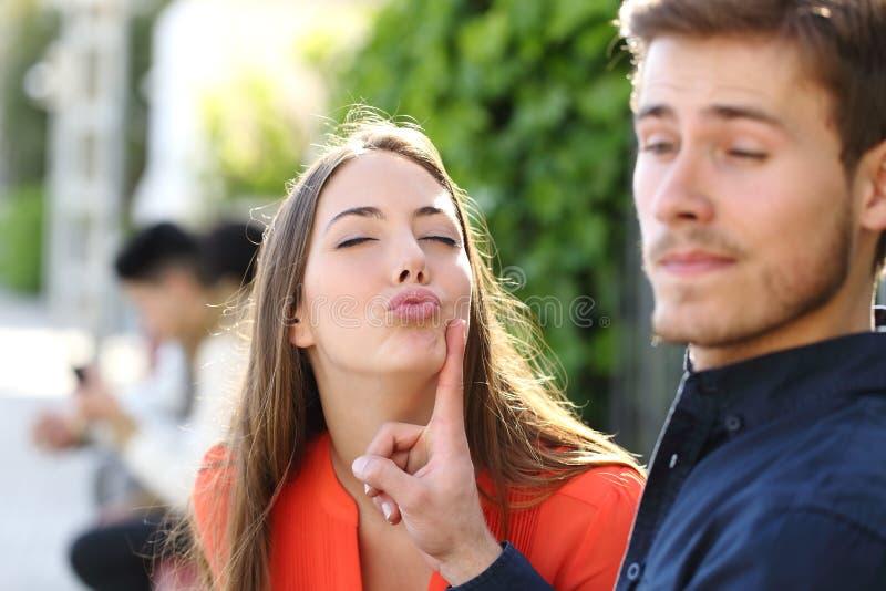 Die Frau, die versucht, einen Mann und ihn zu küssen, weist sie zurück stockbild