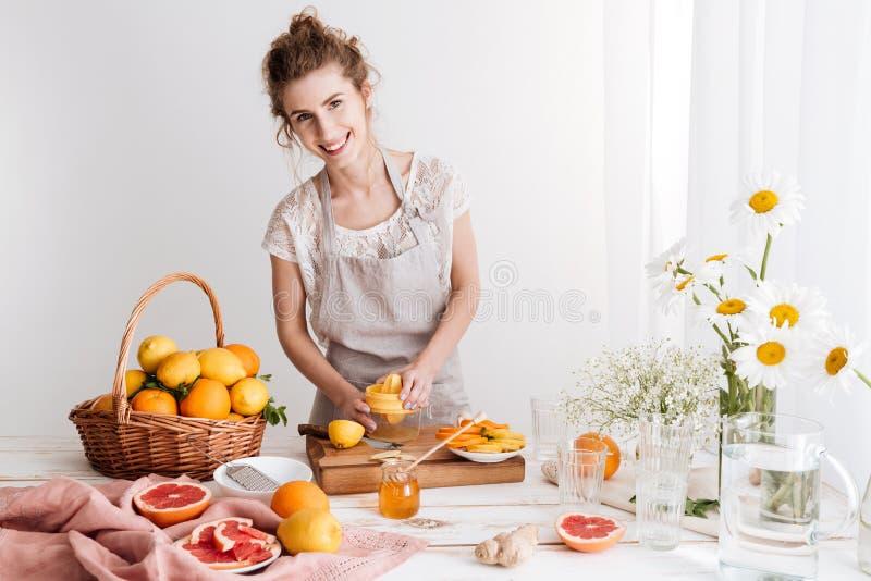 Die Frau, die zuhause steht und drückt heraus Saft von Zitrusfrüchte zusammen stockbild