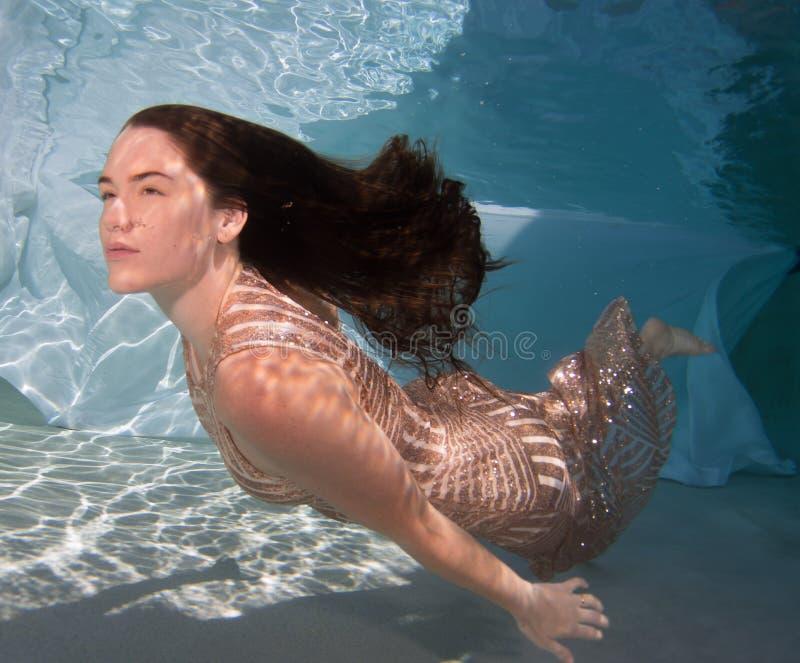 Die Frau, die ein Kleid hält sie trägt, atmen unter Wasser stockfotografie