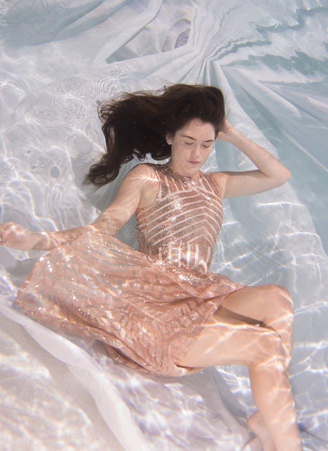 Die Frau, die ein Kleid hält sie trägt, atmen unter Wasser lizenzfreie stockfotos