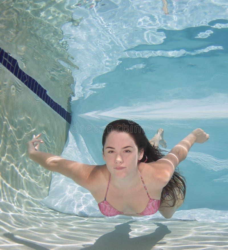 Die Frau, die einen Bikinibadeanzug hält sie trägt, atmen unter Wasser stockfotos