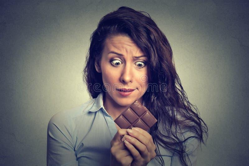 Die Frau ermüdete von den Diätbeschränkungen Bonbonschokolade sehnend lizenzfreies stockfoto