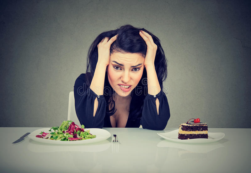 Die Frau ermüdete von den Diätbeschränkungen entscheiden, gesundes Lebensmittel oder Kuchen zu essen, die sie sich sehnt stockbild