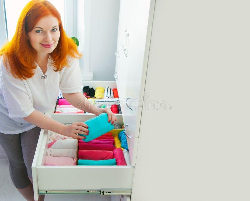 Die Frau faltet T-Shirts im Fach Eine Frau räumt Th auf stockfoto