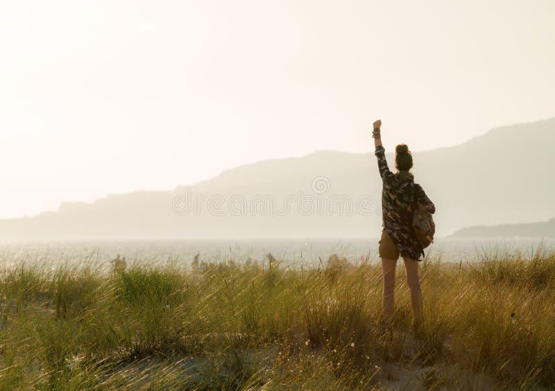 Die Frau, die gegen Berg sich freuen und der Ozean gestalten bei Sonnenuntergang landschaftlich lizenzfreie stockbilder