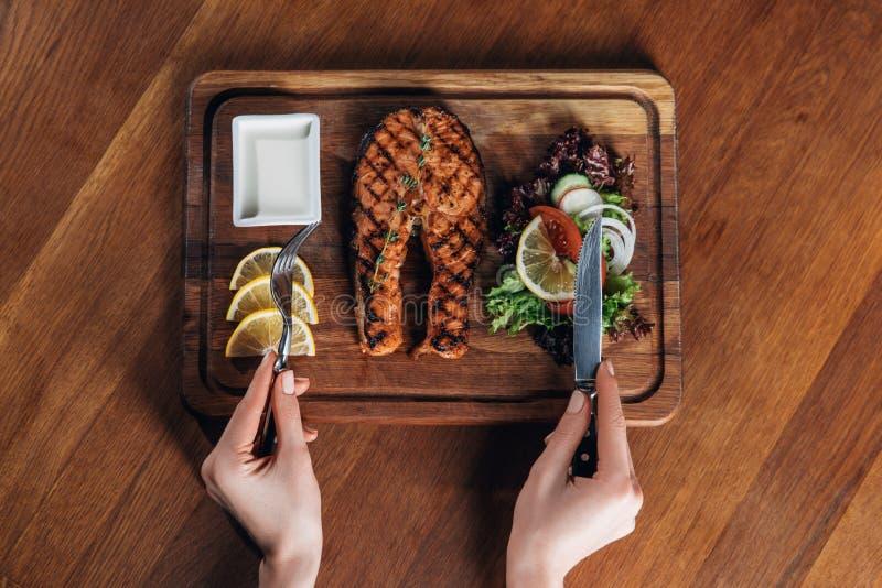 Die Frau, die gegrilltes Lachssteak isst, diente auf hölzernem Brett mit Zitrone und Kopfsalat stockfoto