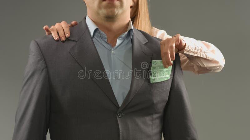 Die Frau, die Geld von nimmt, bemannt Tasche, Betrug und Diebstahl, Konzept der einzelstaatlichen Steuern lizenzfreie stockbilder