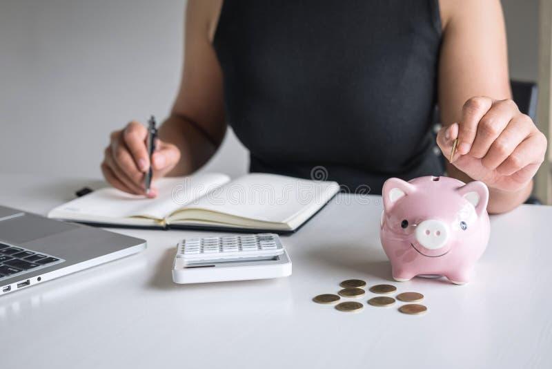Die Frau, die goldene Münze in rosa Sparschwein für einsetzt, steigern wachsendes Geschäft zum Gewinn und Einsparung mit dem Spar lizenzfreie stockfotografie
