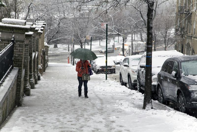 Die Frau hält Regenschirm während des Schneefalles gehend herauf Bronx New York lizenzfreie stockfotos
