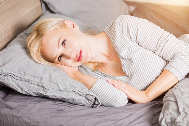 Die Frau, die im Bett nach liegt, wachen auf stockfotografie