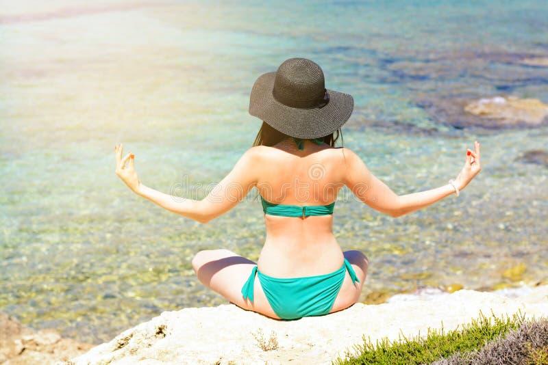 Die Frau im grünen Anzug und im Hut meditiert auf dem Strand im Lotussitz Die Ansicht von der Rückseite lizenzfreie stockbilder