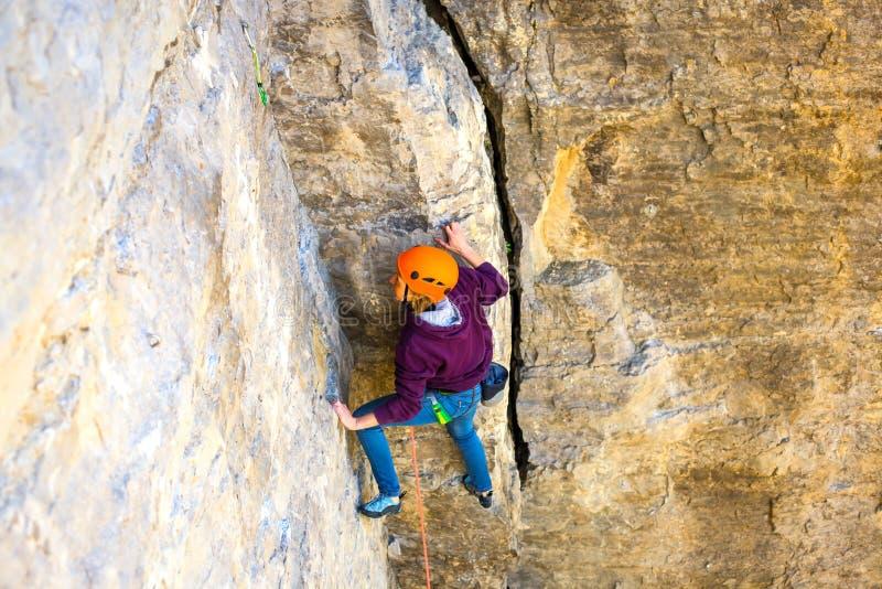 Die Frau im Sturzhelm klettert den Felsen stockbilder