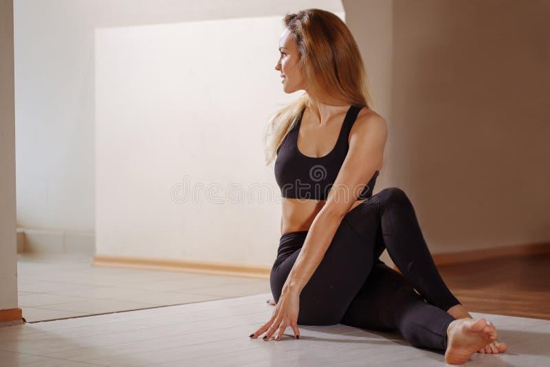 Die Frau, die junges dünnes Sitzmädchen der spinalen Torsion ausdehnt, macht Übung stockfotos