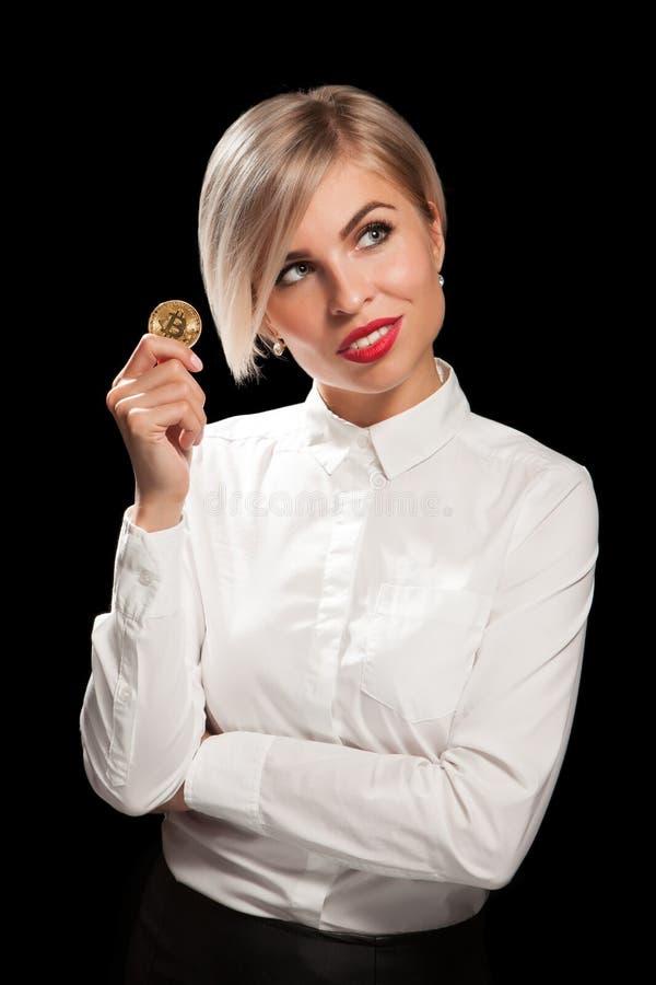 Die Frau, die körperliches bitcoin cryptocurrency hält, prägt in ihren Händen lizenzfreies stockfoto