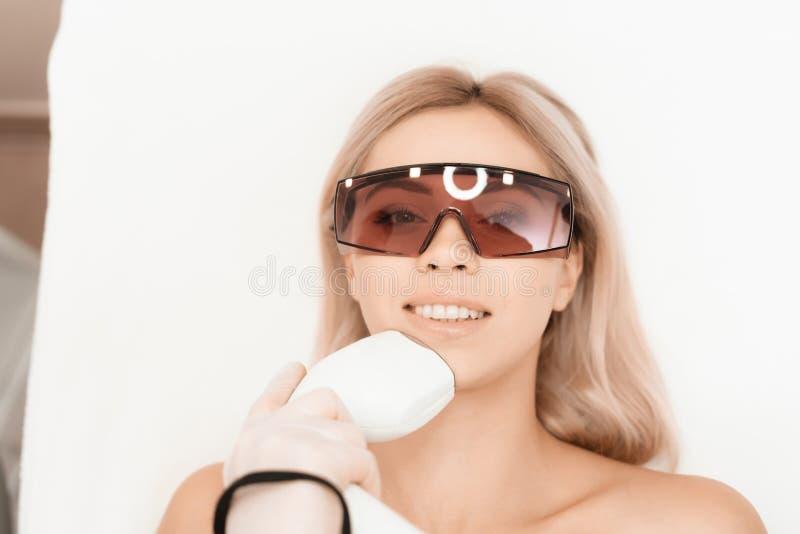 Die Frau kam zum Verfahren des Laser-Haarabbaus Der Doktor behandelt ihr Gesicht mit einem Apparat lizenzfreies stockfoto
