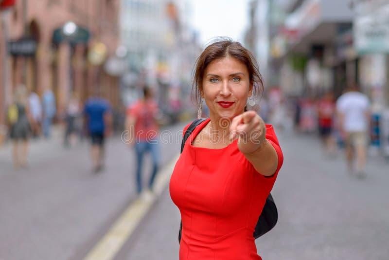 Die Frau kleidete im roten Kleid zeigend auf Kamera an stockfotografie