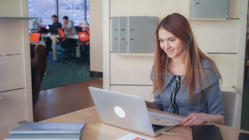 Die Frau mit dem langen roten Haar hat Videoanruf mit Kunden lizenzfreie stockfotos