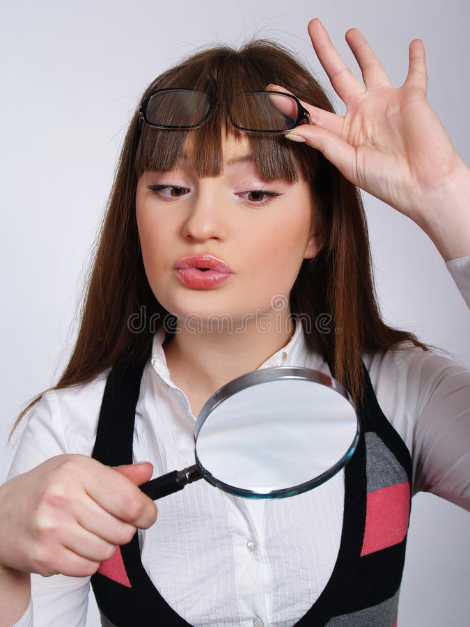 Die Frau mit einem Vergrößerungsglas in einer Hand stockfotos