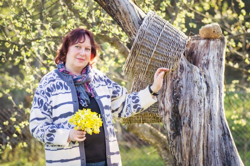 Die Frau, die nahe Baum mit Frühling aufwirft, blüht in der Hand lizenzfreie stockfotografie