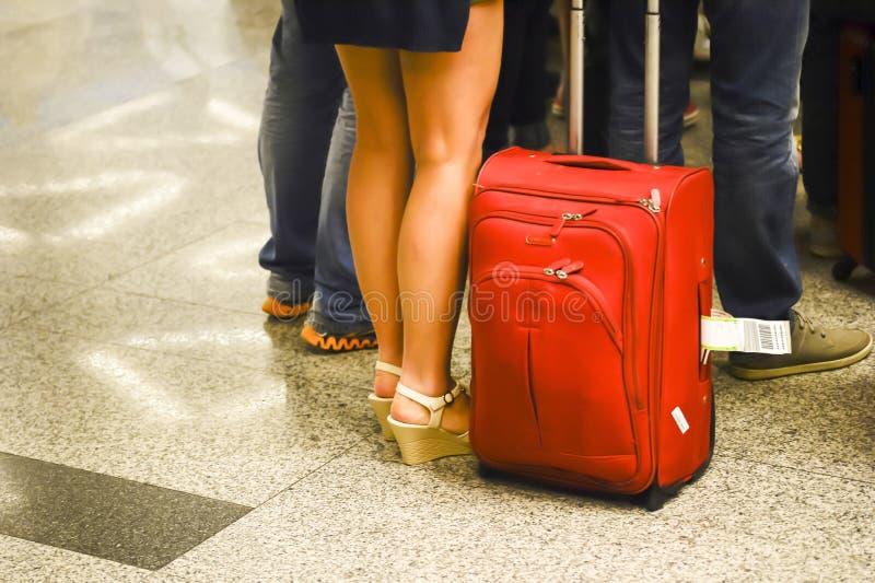 Die Frau ` s Beine mit einem großen roten Koffer dreht an herein den Vordergrund in Erwartung der Landung am Flughafen blurry stockfotografie