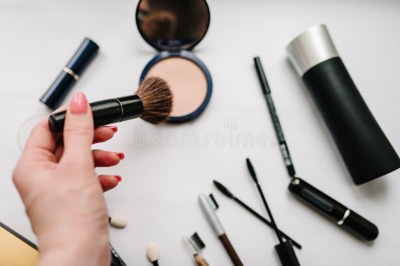 Die Frau ` s Hand hält eine Bürste auf Satz-kosmetischen Produkten des hellen weißen Hintergrundes verschiedenen: Bürsten, Lidsch lizenzfreies stockfoto