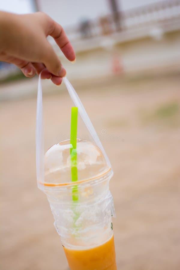 Die Frau ` s Hand hält eine Plastikschale thailändischen Tee, Bild in unscharfem Hintergrund lizenzfreies stockfoto