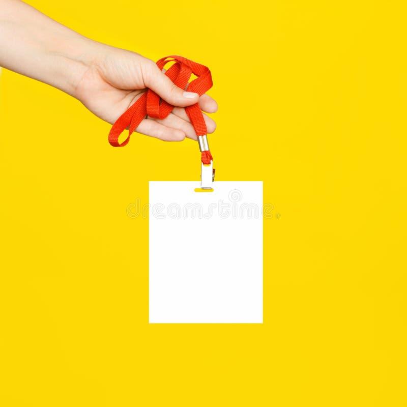Die Frau ` s Hand hält einen sauberen weißen Ausweis auf einer roten Schnur auf gelbem Hintergrund lizenzfreie stockfotos