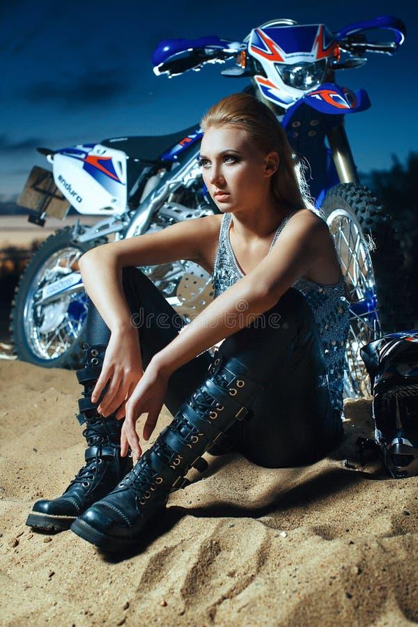 Die Frau sitzt auf Sand nahe dem Motorrad lizenzfreie stockfotografie