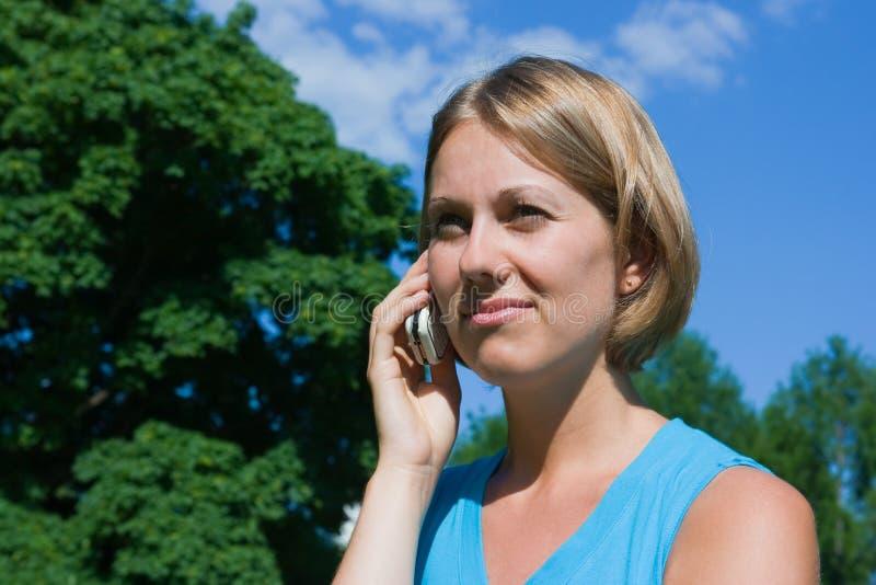 Die Frau spricht durch einen Handy stockbilder