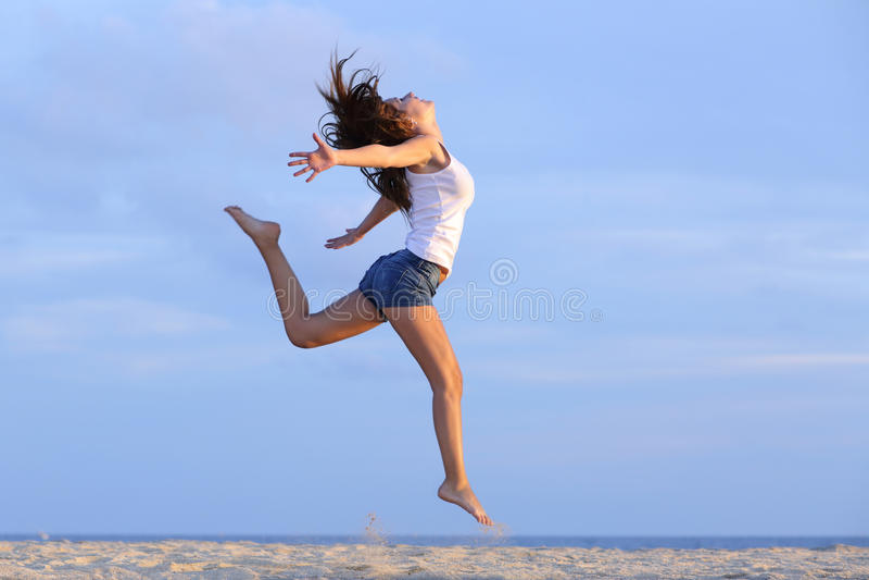 Die Frau springend auf den Sand des Strandes stockbilder