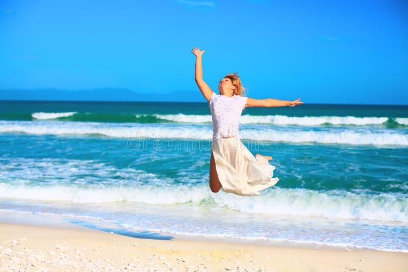 Die Frau springend auf den Strand lizenzfreies stockbild