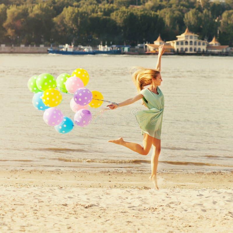 Die Frau springend auf den Strand mit Ballonen lizenzfreie stockfotografie