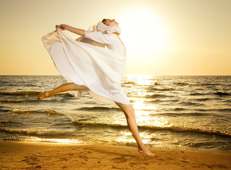 Die Frau springend auf einen Strand lizenzfreies stockfoto