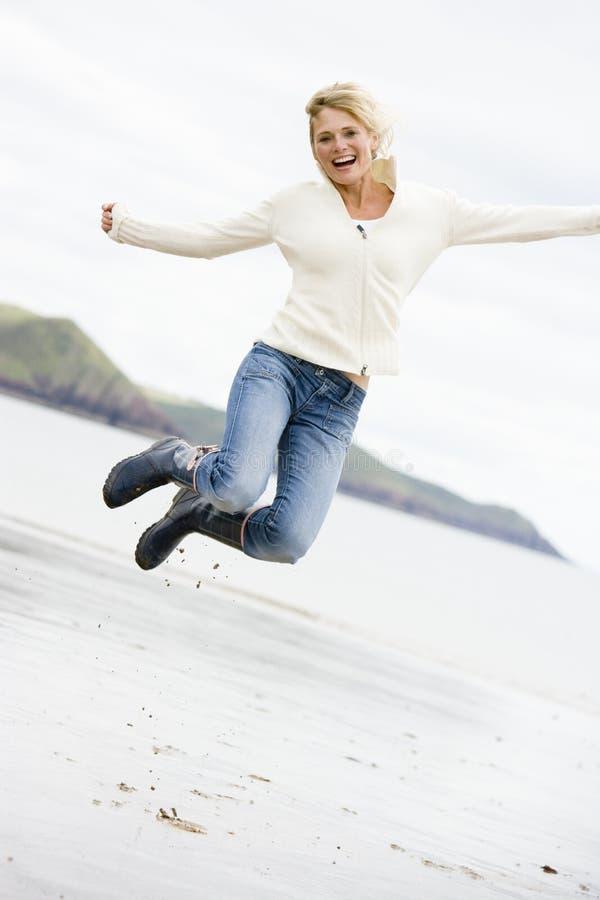 Die Frau springend auf Strand lizenzfreie stockfotografie