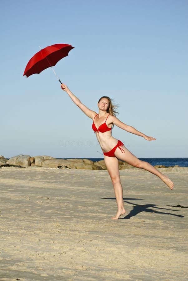 Die Frau springend auf Strand mit rotem Regenschirm stockfoto