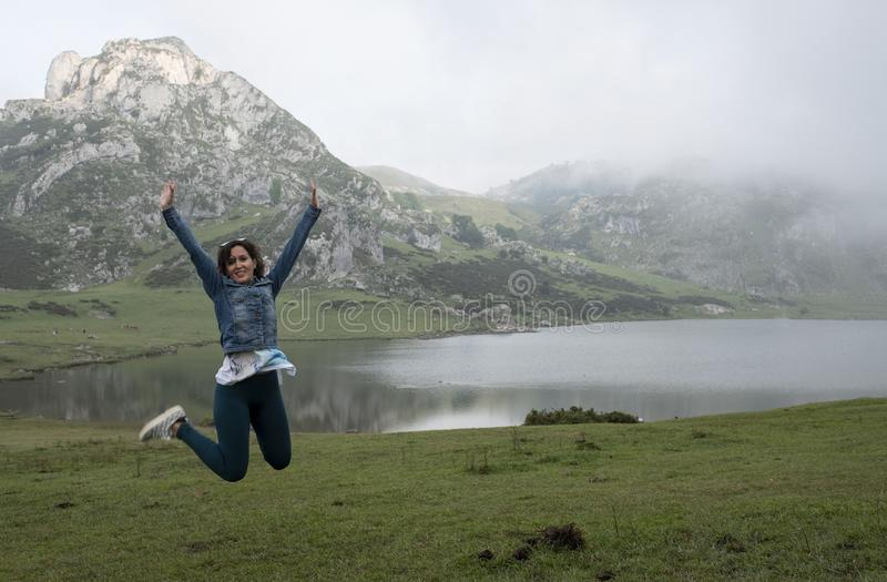 Die Frau springend für Freude vor einem See in einer Gebirgslandschaft, in den Seen von Covadonga stockfotografie