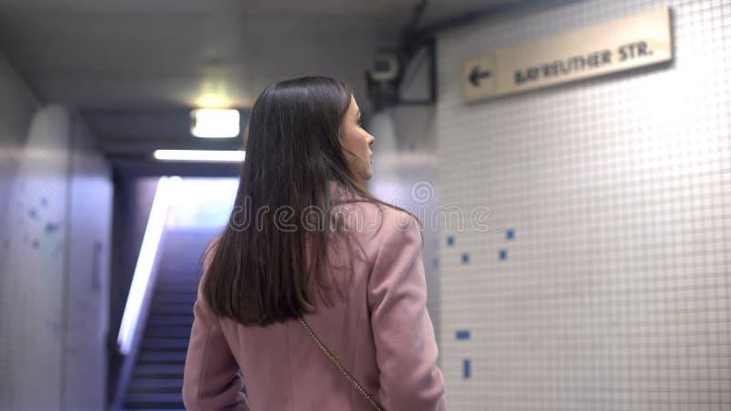 Die Frau, die Straßenzeiger im Untergrund betrachtet, Tourist verlor in der großen unbekannten Stadt stockbilder