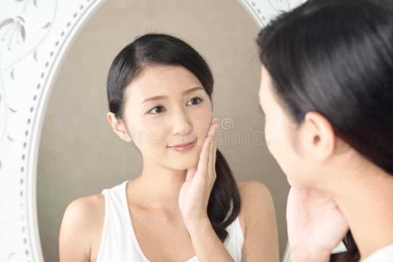Die Frau, die um ihrem Gesicht sich kümmert lizenzfreie stockfotografie