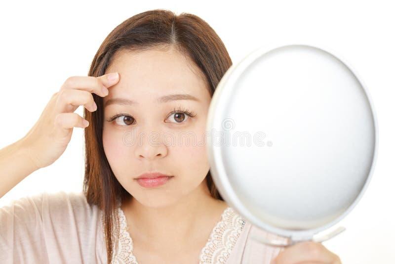 Die Frau, die um ihrem Gesicht sich k?mmert lizenzfreies stockbild