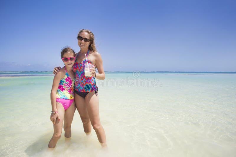 Die Frau und Mädchen, die einen tropischen Strand genießen, machen Urlaub stockfoto