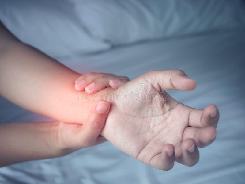 Die Frau, die unter schmerzlichem Gefühl im Arm leidet, mischt zu Hause mit lizenzfreie stockbilder