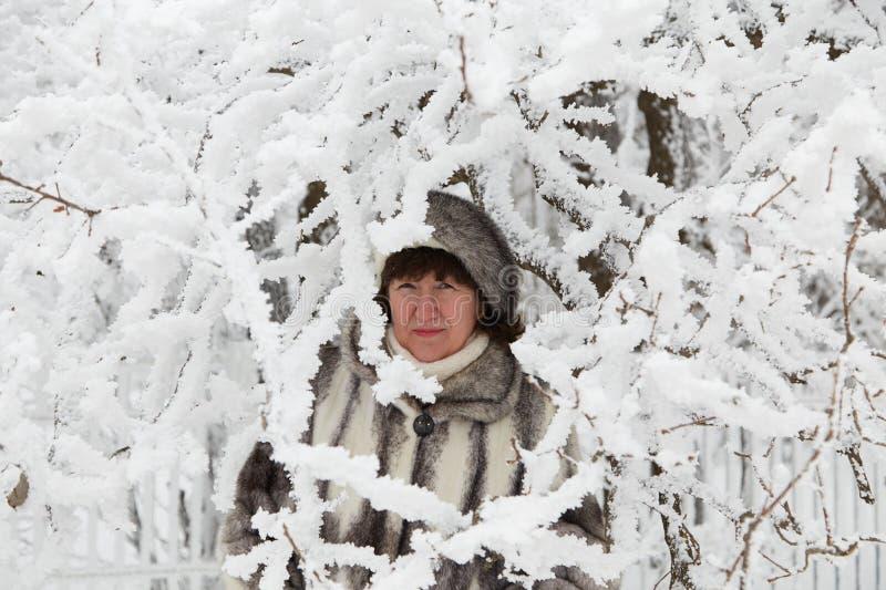 Die Frau unter schneebedeckten Niederlassungen lizenzfreies stockbild