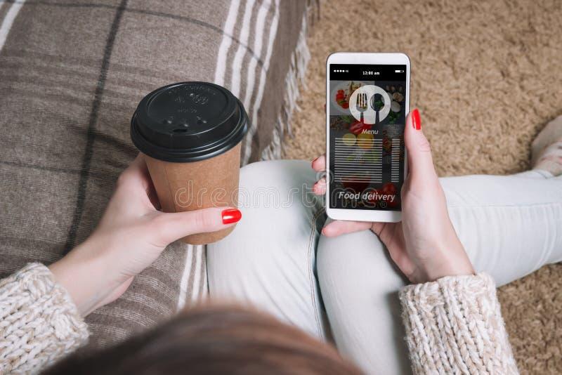 Die Frau verwendet die Anwendung auf dem Mobile, um Nahrungsmittellieferung zu bestellen On-line-Lieferung lizenzfreie stockbilder