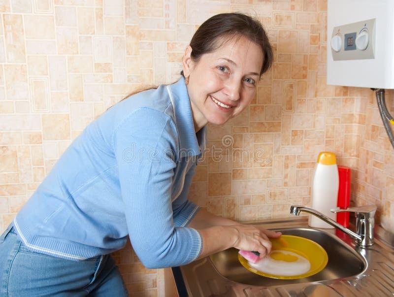 Die Frau wäscht Waren auf Küche stockbilder