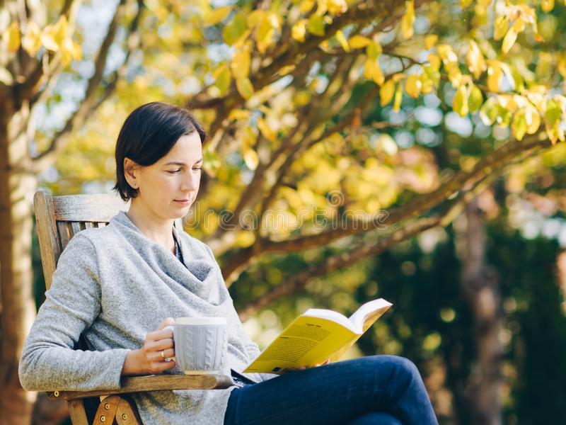 Die Frau, die warmen Knit trägt, kleidet das Trinken einer Schale heißen Tees oder cof lizenzfreies stockbild