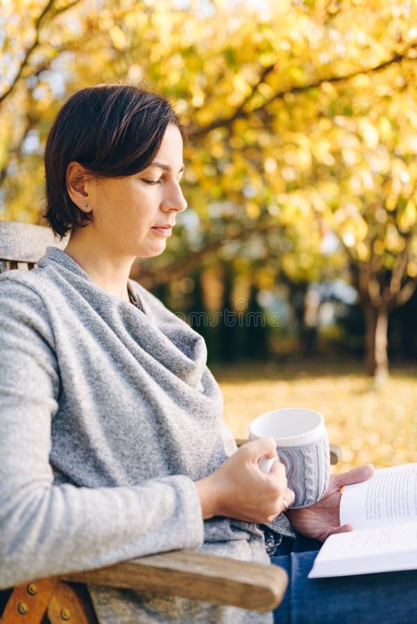 Die Frau, die warmen Knit trägt, kleidet das Trinken einer Schale heißen Tees oder cof stockfotografie