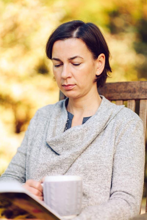 Die Frau, die warmen Knit trägt, kleidet das Trinken einer Schale heißen Tees oder cof stockfoto