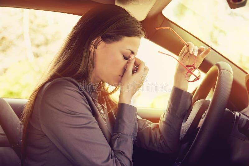 Die Frau, welche die Kopfschmerzen entfernen Gläser hat, muss einen Halt machen, nachdem sie Auto im Stau gefahren hat stockbilder