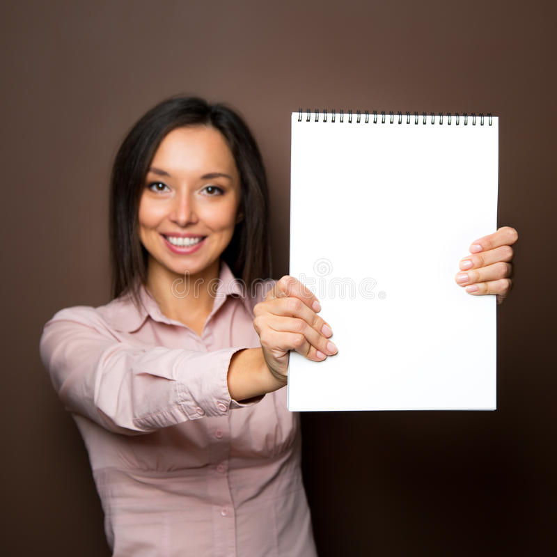 Die Frau zeigend, die weißes leeres Zeichen hält, bekleben Sie Anschlagtafel mit Plakaten lizenzfreie stockbilder