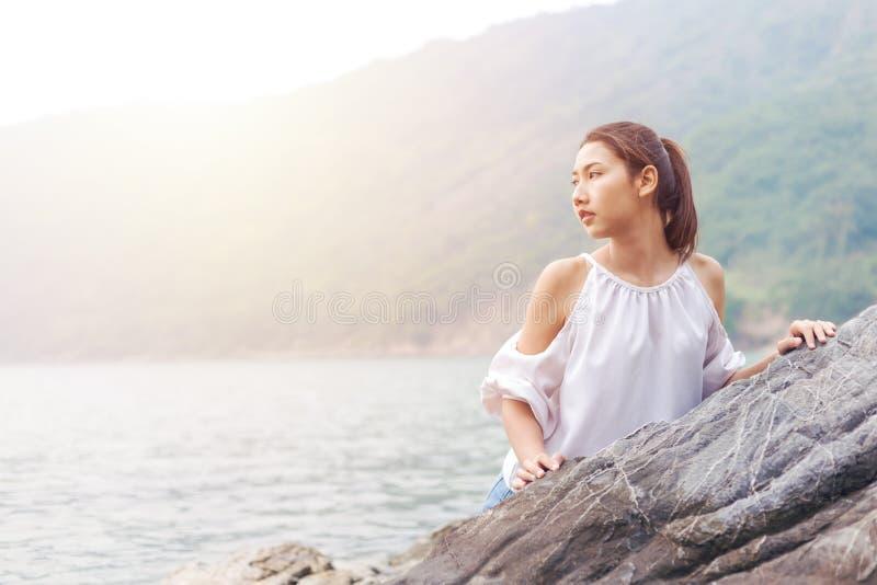 Die Frauen berühren Felsen und Hintergrund mit Gebirgs- und Seewelle sie trägt weißes Kleid und ihr langes Haar stockbilder
